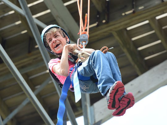 The NEW Zoo Adventure Park zip line hosted a group of physically handicapped adventurists Aug. 11, 2014.  Vicki Nass is hoisted from her wheelchair to the top of the 50-foot zip line tower for her ride.