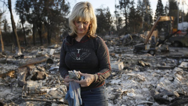 Debbie Wolfe stares at the broken figurine she found in the burned ruins of her home on Tuesday in Santa Rosa, Calif.
