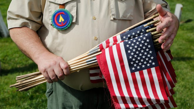 In this 2016 file photo, Scout Master Michael Ream holds bundle of American flags as members of Boy Scout Troop 337 crisscross Rossville Cemetery to place flags on the graves of veterans in honor of Memorial Day.
