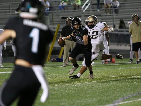 Sharks quarterback Kaden Frost avoids the sack during