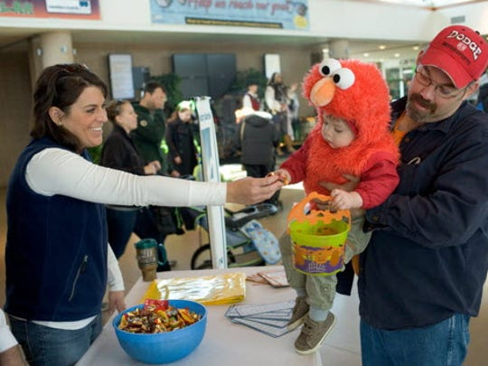 """Dressed as Elmo from """"Sesame Street,"""" Henry Baisley, 2, of West Allis, is tickled to get candy at the Milwaukee County Zoo's Halloween Trick-or-Treat Spooktacular."""