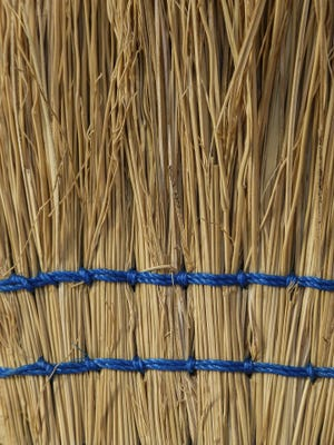 Close-up of a straw broom.