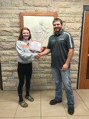 Dr. Ogden Holschbach of Veterinary Associates, Reedsville, hands FFA President Abby Kocourek the check and certificate for the Zoetis Industry Support Program.