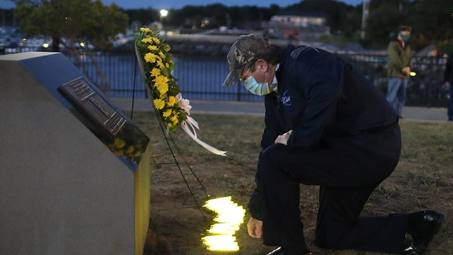 Dan Power of Hingham bends down and places a glow stick at the foot of the POW/ MIA memorial at Whitney Wharf Park after the candlelight vigil there on Friday, Sept. 18, 2020.