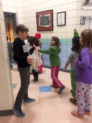 Caleb White gives high-fives to students after the assembly.