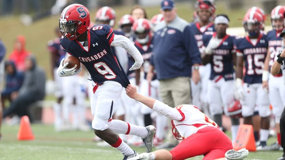 Stepinac's Dexter Chance (9) works to break a tackle