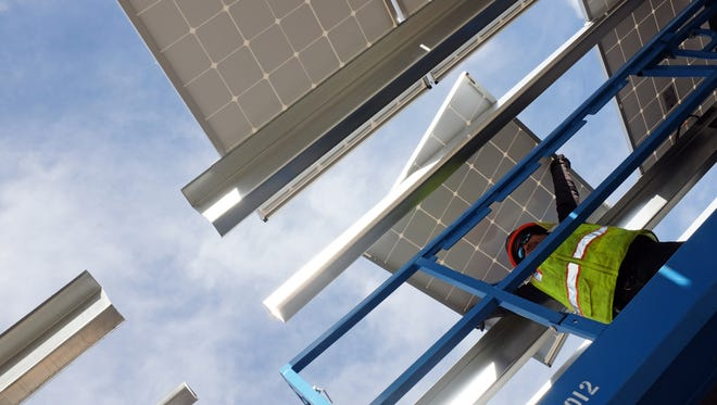 Salvador Yepis of MBL-Energy fits solar panels into place on a structure canopy at Hartnell College in Salinas.