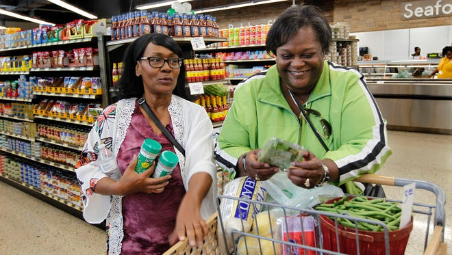 """Loree Williams (left) and Denise Townsend shop at Pete's Fruit Market during the grand opening of the new grocery store.  """"This area was a food desert and now we have something that this community can take advantage of,"""" said Williams."""