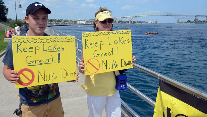 Jan Thomas and her grandson Jake Larowe, of Port Huron, hold signs protesting against a proposed nuclear dump site on Lake Huron in Ontario. A new issue regarding transport of nuclear waste to Port Huron has  caused concern among activists.