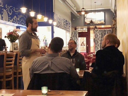 Travis Cook (in apron) speaks with guests at a pop-up dinner in March at Amilinda downtown. The next dinners by pop-up Travisty will be at Birch + Butcher on May 27.