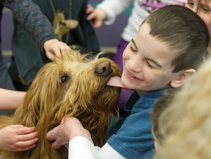 Mater sneaks a kiss with Tyler Hoffner, 6, during the dogs visit to the classroom. A group of therapy dogs visited kindergarten classes at Oak Trace Elementary School in Westfield Friday, Feb. 28, 2014.