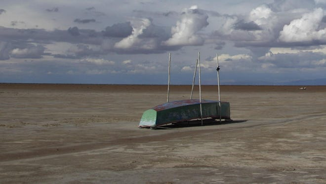 In this Jan. 12, 2016 photo, an abandoned boat lies on the dried up lake bed of Lake Poopo, on the outskirts of Untavi, Bolivia.