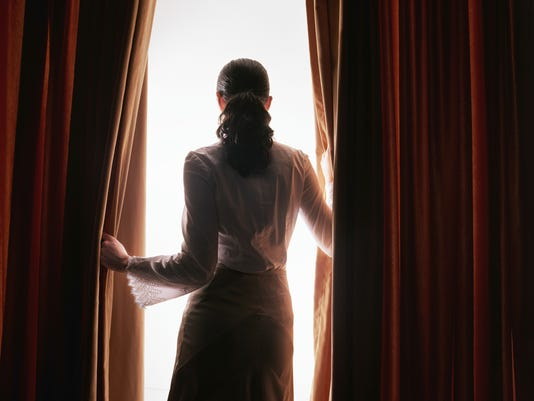 Young woman looking through red curtains, rear view