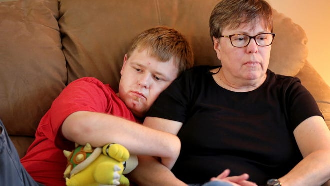 Debbie House, of Amelia, sits with her son, Kevin, 20, to talk about the lawsuit she filed against West Clermont Local School District and Union Township for violating Kevin's rights and Ohio Law on September 11, 2014 during school. Kevin is autistic. House said since the incident, Kevin has regressed and now carries a stuffed animal, Bowser, for safety.