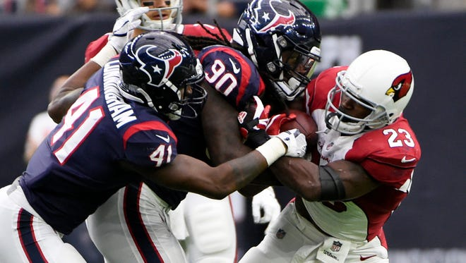 Arizona Cardinals running back Adrian Peterson (23) is stopped by Houston Texans defenders Jadeveon Clowney (90) and Zach Cunningham (41) during the second half of an NFL football game Sunday, Nov. 19, 2017, in Houston.