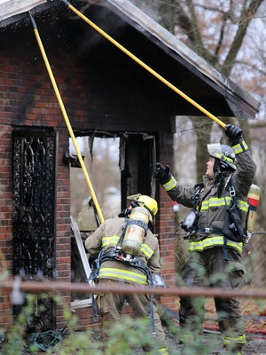 Firefighters work a house fire at 4017 College St. Ext. in Milan, Tenn., on Monday, Jan. 2, 2017.