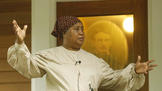 Reva Golden portrays Harriet Tubman, an escaped slave who became an abolitionist and political activist, as she speaks Friday from the front porch of the John Brown House during a Juneteenth celebration.
