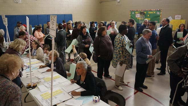 Voters form lines as they wait to have their ballots scanned in voting machines at the Myron Francis elementary school polling place in Rumford in 2016.