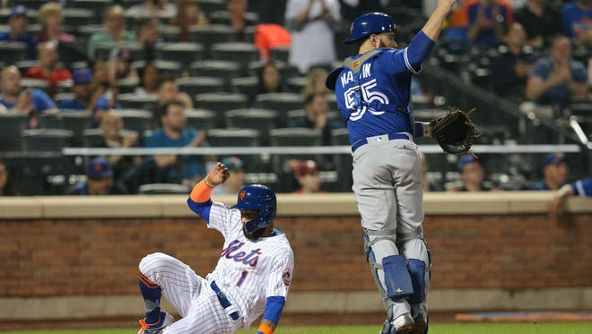 New York Mets shortstop Amed Rosario (1) scores against Toronto Blue Jays catcher Russell Martin (55) on a double by New York center fielder Juan Lagares (not pictured) during the fourth inning at Citi Field.