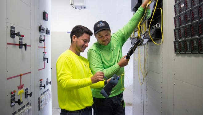 George Liscio (right) and Cesar Rodriguez, fiber optic technicians with Precision Contracting Services, troubleshoot an outage at an electrical substation in Vero Beach.