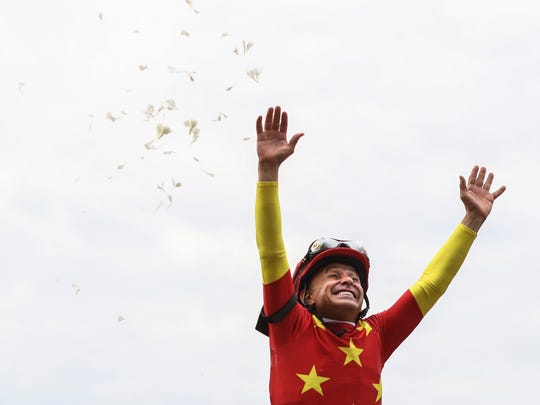 Jockey Mike Smith celebrates aboard Justify after capturing the Triple Crown after winning the Belmont Stakes June 9, 2018 at Belmont Park in Elmont, NY.
