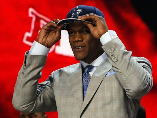 FILE - In this May 1, 2015, file photo, Nebraska defensive lineman Randy Gregory holds a Dallas Cowboys cap on his head after being selected by Dallas in the second round of the NLF football draft in Chicago. Gregory failed a marijuana test at the NFL scouting combine in February 2015 and later publicly acknowledged his use in college. Once considered a high first-round draft pick, he wasn't selected until late in the second round by Dallas. (AP Photo/Charles Rex Arbogast, File)