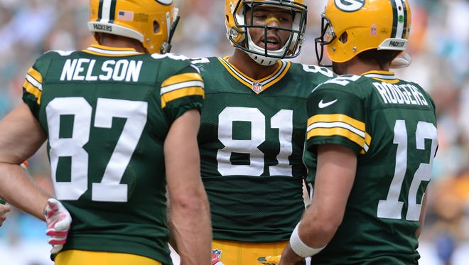 Green Bay Packers tight end Andrew Quarless (81) talks with quarterback Aaron Rodgers (12) and Jordy Nelson (87) against the Miami Dolphins at Sun Life Stadium October 12, 2014.