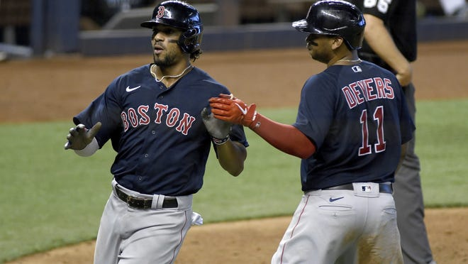 Boston Red Sox's Rafael Devers, right, and Xander Bogaerts celebrate after scoring during the sixth inning of a baseball game against the Miami Marlins, Thursday, Sept. 17, 2020, in Miami.