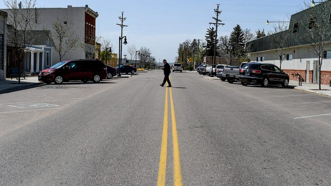 A man crosses the street in quiet downtown Timnath, Wednesday, April 15, 2015.