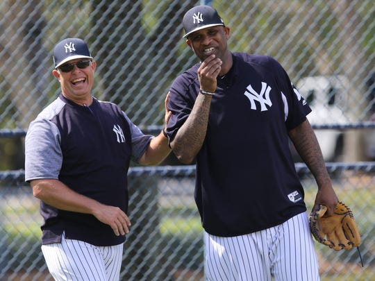 A coach and pitcher CC Sabathia have a laugh as the pitchers practiced defense.