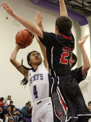 Mescalero's Alex Kaydahzinne, left, puts up a shot while being defended by two Cliff players.