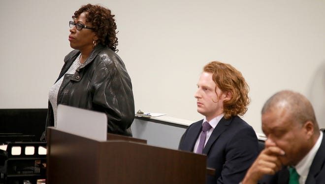Lela Whitfield stands up to speak about her impending eviction from her childhood home, during court hearing with Fannie Mae, who has rights to the home, at the 36th District Court in Detroit on Friday, Nov. 13, 2015. Matthew Clark, her lawyer, center, and Trott and Trott lawyer representing Fannie Mae, Kevin Hammons, looks on.
