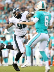 Eagles defensive end Derek Barnett reaches too late for a pass from Dolphins quarterback Jay Cutler.