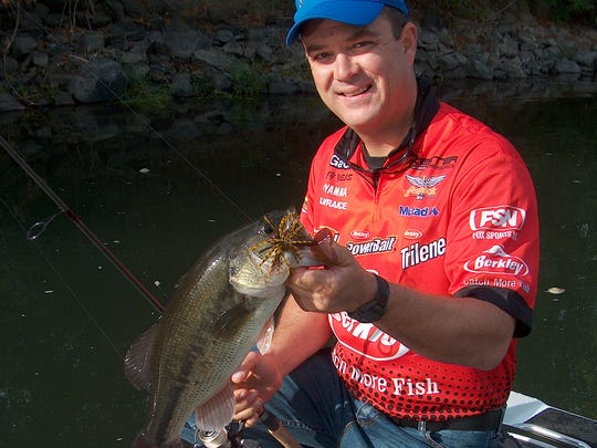 Bass-fishing professional Jay Yelas of Corvallis poses with a Willamette River largemouth bass.