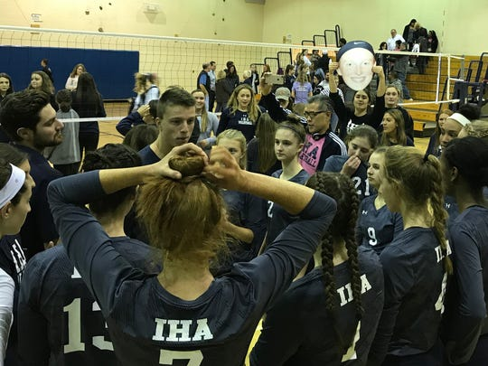Immaculate Heart huddles up after defeating NV/Old Tappan, 2-0, in the Bergen County girls volleyball semifinals on Friday. Blue Eagle fans showed their support with posters of the players' faces.