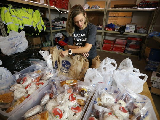 Ellen Hudson packages food items for delivery as she