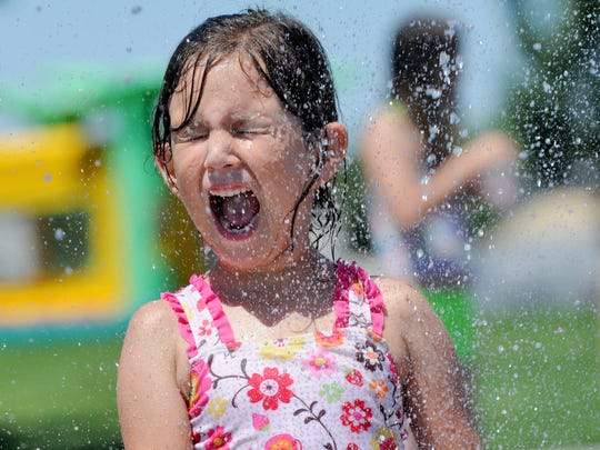 Kayla Holdridge is sprayed with water at Settlers Park