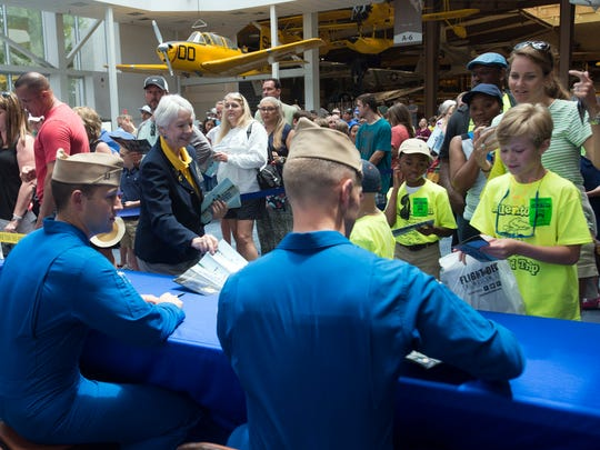 Volunteer Sara Parkin, back left, watches over an autograph session on Wednesday, April 19, 2017, at the National Naval Aviation Museum at Pensacola Naval Air Station.