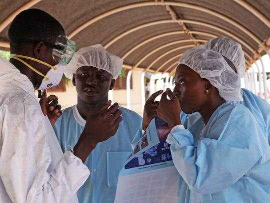 A  health worker, right, briefs another on the use