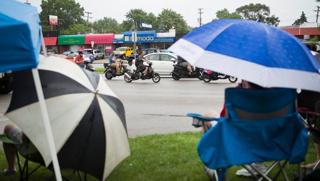 Cruise goers shield themselves from the rain and watch drivers head down Woodward.