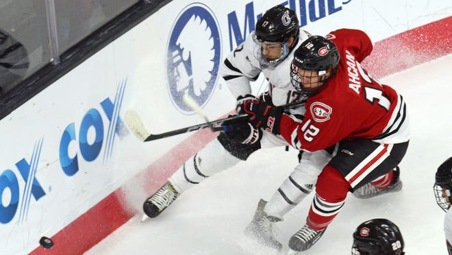 Nebraska Omaha's David Pope (left) battles St. Cloud State defenseman Jack Ahcan for the puck during a game.