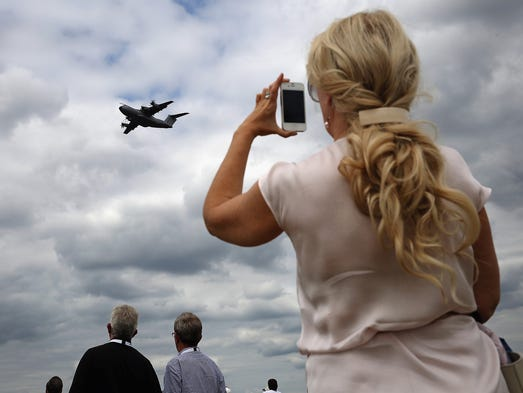 A visitor photographs a flying display at the Farnborough International Airshow on July 16 in Farnborough, England.