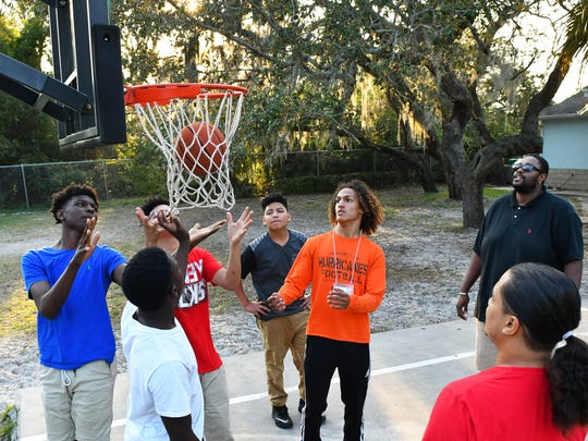 Teens play basketball with mentor A.J. Edwards, far right, at the Brevard Neighborhood Development Coalition DOCK community center in Melbourne's Booker T. Washington neighborhood.