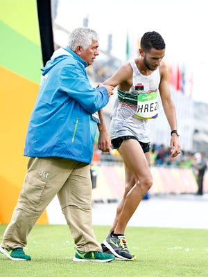 Mo Hrezi of Libya receives assistance after crossing the finish line of the men's Marathon race of the Rio 2016 Olympic Games Athletics, Track and Field events at the Sambodromo in Rio de Janeiro, Brazil, 21 August 2016.