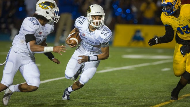 Naples quarterback Jordan Persad-Tirone looks for an opening as Northwestern's defense closes in at the Nathaniel Traz-Powell stadium in Miami, where the Naples Golden Eagles took on the Northwestern Bulls on Friday, Dec. 1, 2017.