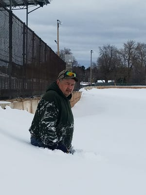 Shawano Speedway's Bob Reiter stands on the frontstretch in waist-high snow early last week. Sun, wind and warmer temperatures are desperately needed if Shawano Speedway is going to be able to open its season at 6:30 p.m. Saturday.