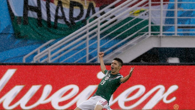 Mexico's Oribe Peralta celebrates after scoring the opening goal during the group A World Cup soccer match between Mexico and Cameroon in the Arena das Dunas in Natal, Brazil, Friday, June 13, 2014.