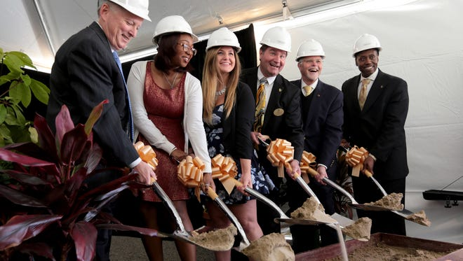 From left, Richard Devore, Vice Chair OU Board of Trustees, Shayne Hearns, School of Nursing Student, Alexandra Nixon, former resident assistant, James Zentmeyer, Director, University Housing, George Hynd, President Oakland University, Glenn Macintosh, Vice President, Student Affairs, hold up shovels with sand in a symbolic gesture at the ground breaking ceremony for new student housing at Oakland University on June 8, 2016.