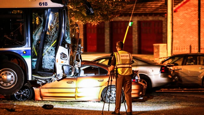 Investigators document the scene of a bus accident at the corner of N. Pennsylvania and Oakland avenues in Lansing Thursday evening, Oct. 6, 2016.  At least one other vehicle was involved.  Officials say about a dozen people were injured.  The accident remains under investigation.