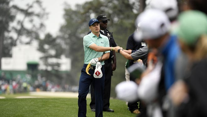 Jordan Spieth bumps fists with fans as he walks to the 7th hole during a practice round at Augusta National Golf Club on April 5.